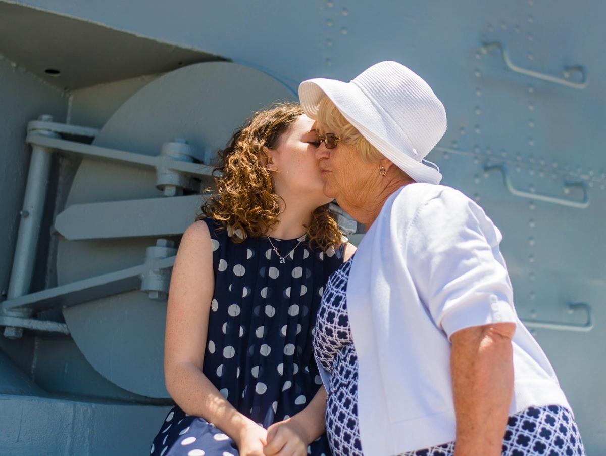 古希祝いで祖母の頬にキスする孫娘