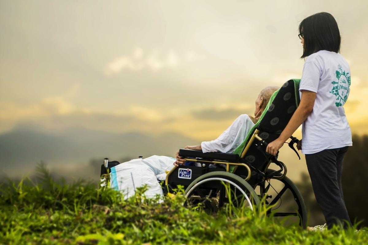 施設利用者を車椅子で散歩させている介護士